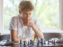 逗人喜爱,聪明,11岁白色衬衫的男孩在教室坐并且下在棋枰的棋 训练,教训,爱好, 免版税库存照片