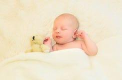 逗人喜爱婴儿睡觉与在床家的玩具熊玩具一起 免版税库存照片