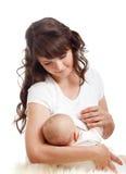 逗人喜爱婴孩的乳房喂养她的母亲 免版税库存图片