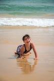 逗人喜爱年轻小女孩笑的放置在沙子的泳装在海滩 图库摄影