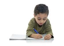 逗人喜爱年轻男小学生学习 库存照片