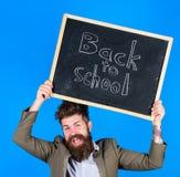 逗留正面 老师有胡子的人拿着有题字的黑板回到学校蓝色背景 老师与 免版税库存照片