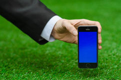 通信和企业主题:在拿着有蓝色屏幕的一套黑衣服的手一个现代电话在绿草背景中  免版税图库摄影