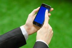 通信和企业主题:在拿着有蓝色屏幕的一套黑衣服的手一个现代电话在绿草背景中  库存图片