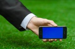 通信和企业主题:在拿着有蓝色屏幕的一套黑衣服的手一个现代电话在绿草背景中  库存照片