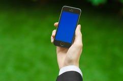 通信和企业主题:在拿着有蓝色屏幕的一套黑衣服的手一个现代电话在绿草背景中  免版税库存图片