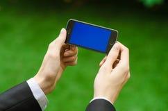 通信和企业主题:在拿着有蓝色屏幕的一套黑衣服的手一个现代电话在绿草背景中  图库摄影