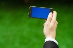 通信和企业主题:在拿着有蓝色屏幕的一套黑衣服的手一个现代电话在绿草背景中  免版税库存照片