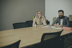 通信和合作与同事 肉欲的妇女和有胡子的人微笑在业务会议上 愉快的商业 免版税库存图片