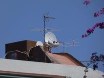 通信天线关于屋顶的在天空蔚蓝 库存照片