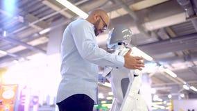 通信机器人和人 一个人拥抱一个妇女机器人 现代机器人技术 女性机器人和人情感 股票录像
