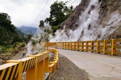 通入蒸汽的山和高速公路有橙色边界的 自然开水在温泉城 免版税库存图片