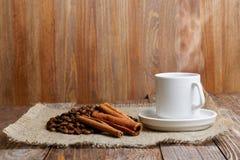 通入蒸汽的杯子热的咖啡、咖啡豆和桂香 免版税库存照片