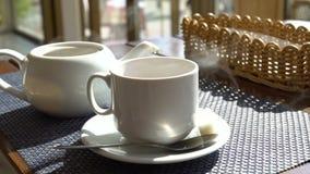 通入蒸汽的白色杯子杯子在桌上的茶咖啡在咖啡馆 热的饮料 影视素材