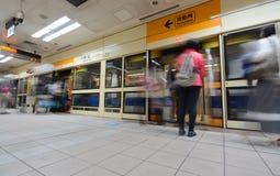 通勤者冲上火车在台北` s橙色MRT地铁线的新庄驻地 免版税库存照片