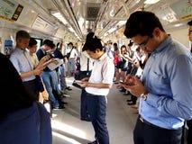 通勤者或乘客在MRT里面通过打比赛通过时间,观看的录影,检查他们的电子邮件或更新他们的soc 免版税库存图片