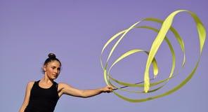 通胀的问题 健康问题 妇女体操运动员漩涡在蓝天背景的绿色丝带 免版税库存照片