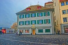 通过一个典雅的大厦的人们在美丽如画的方形的Muhlenplatz 免版税图库摄影