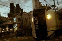 通过一个平交路口的一列高速成田快车在新宿区 免版税库存照片