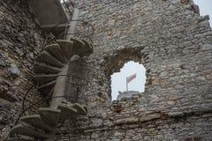 通过一座被破坏的城堡的窗口被看见的波兰的旗子在有薄雾的天气的 免版税图库摄影