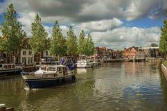 通过一条沿途有树的宽运河的小船在晴天在韦斯普 免版税库存图片
