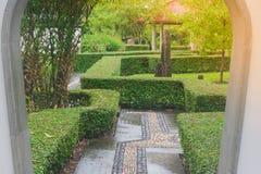 通过中国庭院从白色门道入口有在公园的阳光背景 库存图片
