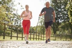 通过乡下一起跑的健康资深夫妇享用 免版税库存图片