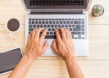 通过使用在木书桌上的一台便携式计算机一个人工作 免版税图库摄影