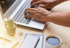 通过使用在木书桌上的一台便携式计算机一个人工作 库存图片
