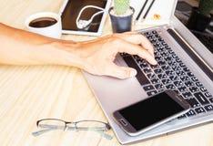 通过使用在木书桌上的一台便携式计算机人工作 免版税库存图片