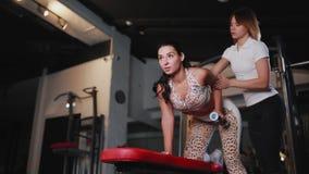 通过使用在长凳的哑铃个人女性教练员监测锻炼的正确施行 回到发型她的妇女 影视素材