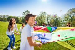 通过使用彩虹降伞,男孩投掷的球  免版税库存照片
