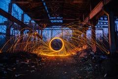 通过使用转动的灼烧的钢丝绒的在被放弃的未完成的工厂厂房的Freezelight和烟火制造术 免版税库存图片