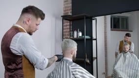 通过使用hairclipper, Tattoed理发师做顾客的理发在理发店,人` s理发和刮在 股票视频