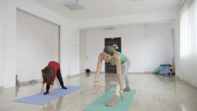 通过做瑜伽锻炼照顾教的健康生活方式在有她逗人喜爱的小女孩女儿的一个明亮的演播室慢动作的- 股票录像