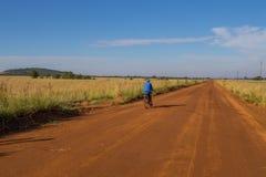 通过农村乡下供以人员在土路的周期 免版税库存图片