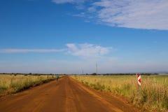 通过农村乡下供以人员在土路的周期 库存照片