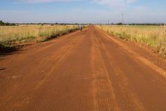 通过农村乡下供以人员在土路的周期 库存图片