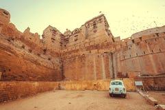 通过历史Jaisalmer堡垒的老白色汽车停车处与石塔在塔尔沙漠 免版税库存照片