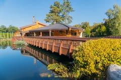 通过在一个池塘的木头一座美丽的桥梁在导致咖啡馆的美丽的景色的公园与夏天大阳台的 库存照片