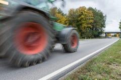 通过在一条国道,德国的拖拉机 免版税图库摄影