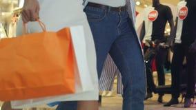 通过在五颜六色的服装的一家服装店走两个女孩的低射击  影视素材