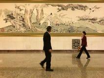 通过在人的大厅的一幅国画的夫人和一个人在北京 库存照片
