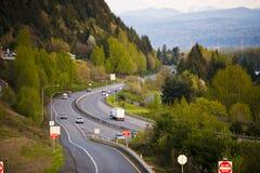 通过在多山森林地西北部的高速公路 免版税图库摄影