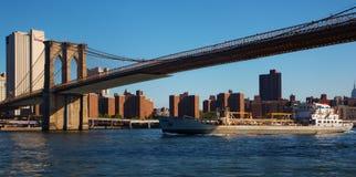 通过在布鲁克林大桥下的货船 免版税图库摄影