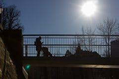 通过在有上面太阳和蓝天的一座桥梁的人们 库存图片