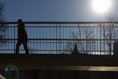 通过在有上面太阳和蓝天的一座桥梁的人们 库存照片