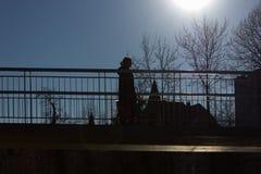 通过在有上面太阳和蓝天的一座桥梁的人们 免版税库存照片