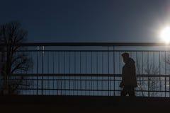 通过在有上面太阳和蓝天的一座桥梁的人们 免版税图库摄影