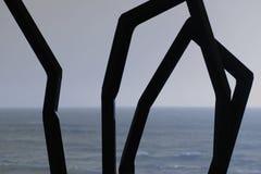 通过在海滩的一些钢棍被看见的海 免版税库存照片